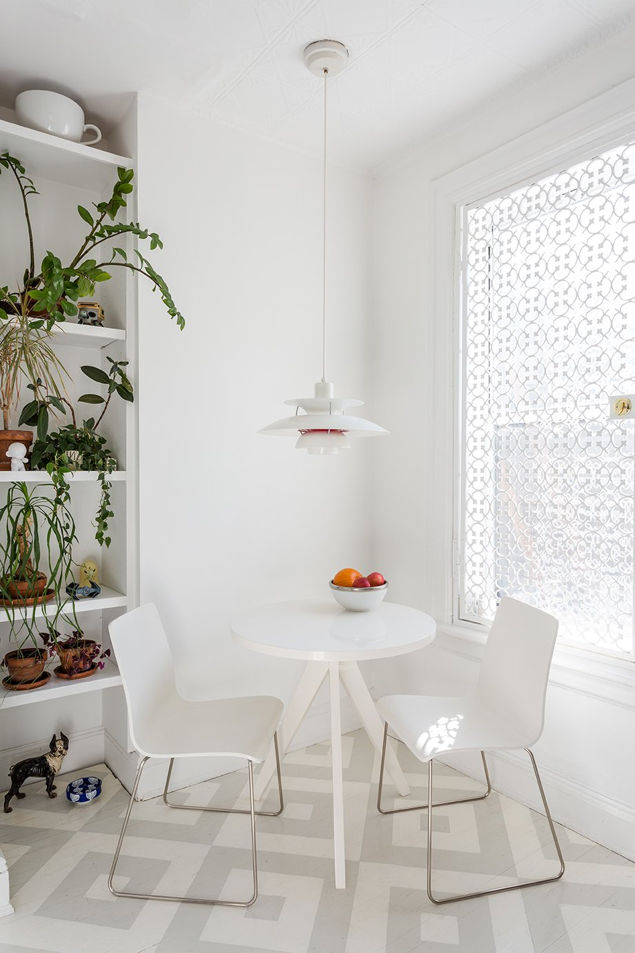In the kitchen, a PH 50 pendant by Poul Henningsen for Louis Poulsen hangs overhead; the window is covered in a decorative cast-iron metal security grate from King Architectural Metals. The painted patterned floor is by Lillian Heard Studio. - Brooklyn, New York Dwell Magazine : July / August 2017 Tagged: Dining Room, Chair, Pendant Lighting, Table, and Painted Wood Floor.  Photo 8 of 13 in A Pair of Designers Renovate Their Brooklyn Brownstone With a Bright Monochromatic Palette
