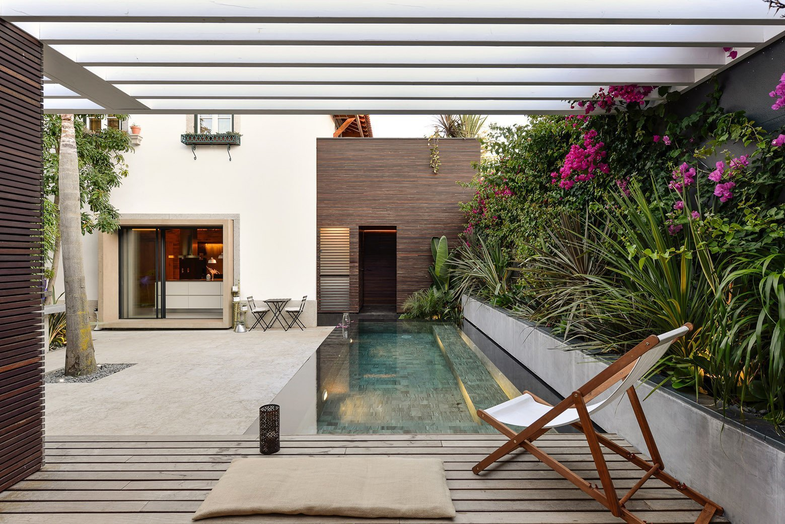 Tagged: Outdoor, Trees, Back Yard, Gardens, Small Pools, Tubs, Shower, Decking Patio, Porch, Deck, Wood Patio, Porch, Deck, and Infinity Pools, Tubs, Shower.  Photo 1 of 16 in An Architect Renovates His 1920s Home in Portugal, While Preserving the Exterior Shell