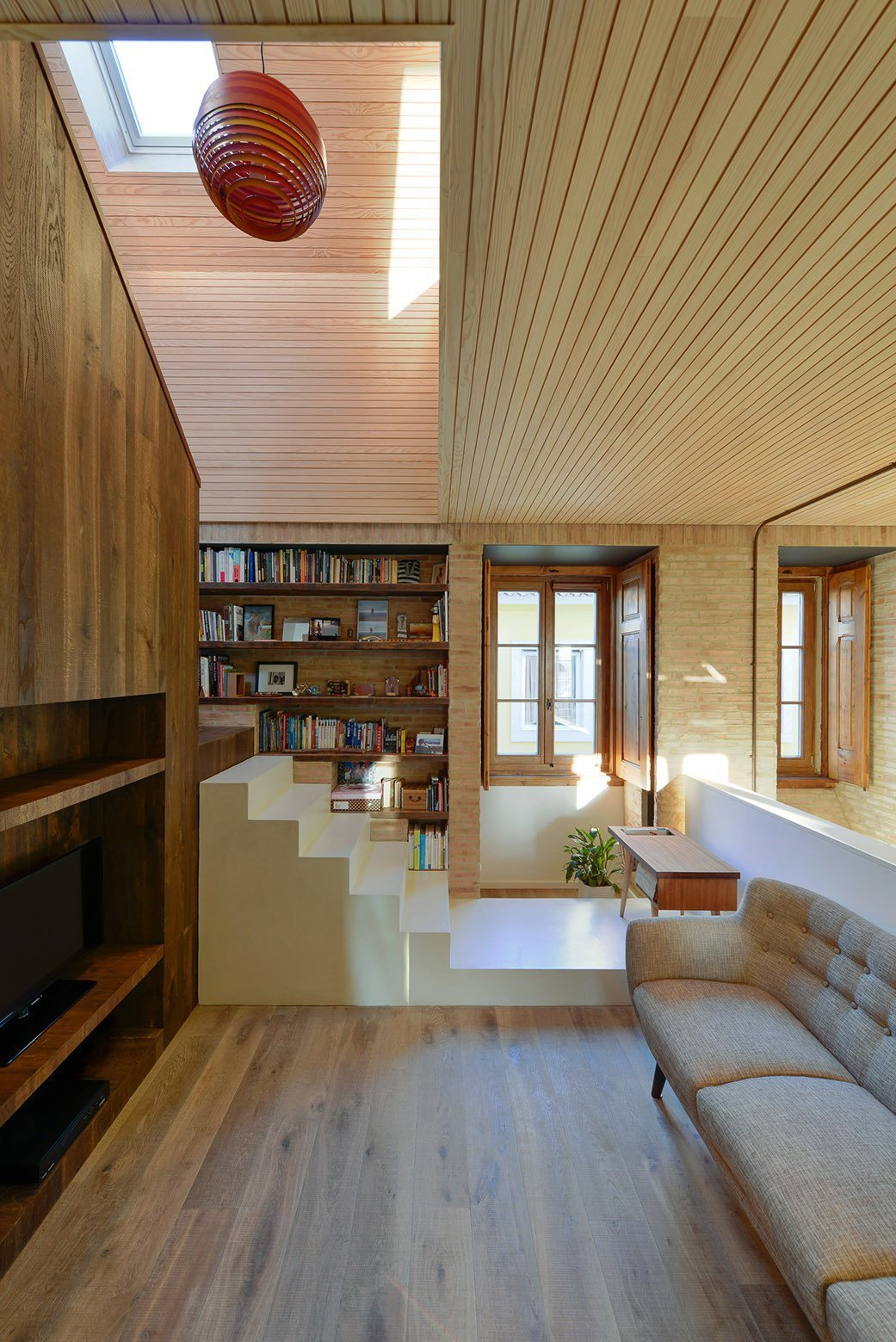 Tagged: Living Room, Bookcase, Light Hardwood Floor, Shelves, Sofa, and Pendant Lighting.  Photo 5 of 16 in An Architect Renovates His 1920s Home in Portugal, While Preserving the Exterior Shell