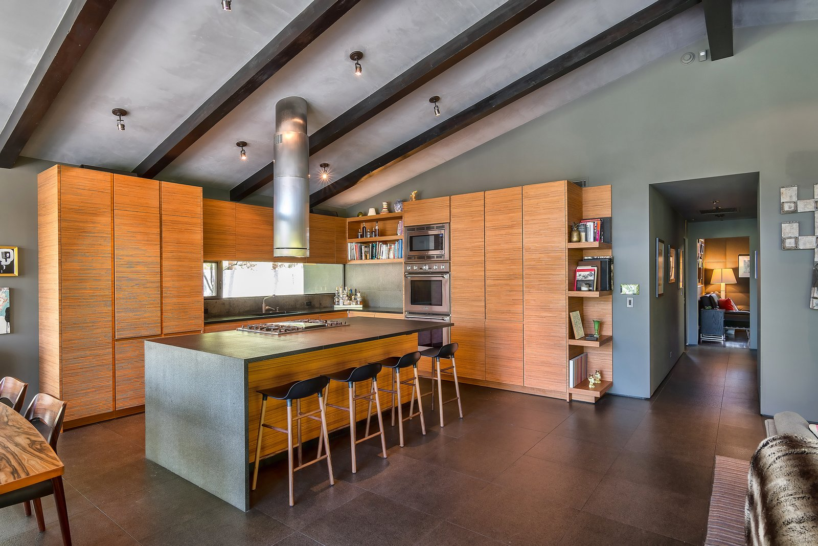 Tagged: Kitchen, Wood Cabinet, Ceiling Lighting, Range, Wall Oven, Stone Counter, and Drop In Sink.  Photo 6 of 14 in John Legend and Chrissy Teigen's Former Midcentury Home in the Hollywood Hills Is For Sale