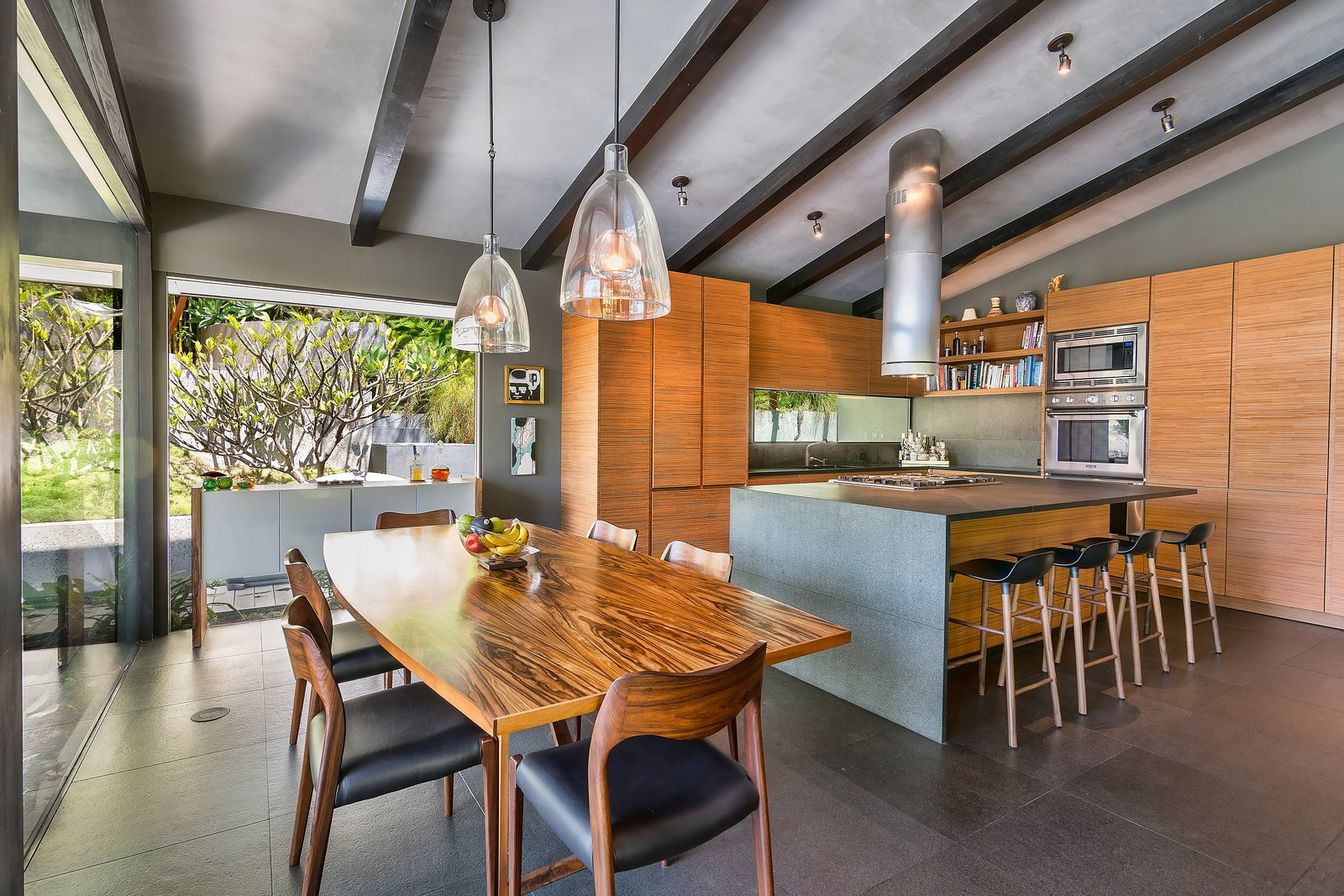 Tagged: Chair, Table, Pendant Lighting, Stools, Storage, Kitchen, Stone Counter, Wall Oven, Drop In Sink, Wood Cabinet, and Range.  Photo 5 of 14 in John Legend and Chrissy Teigen's Former Midcentury Home in the Hollywood Hills Is For Sale