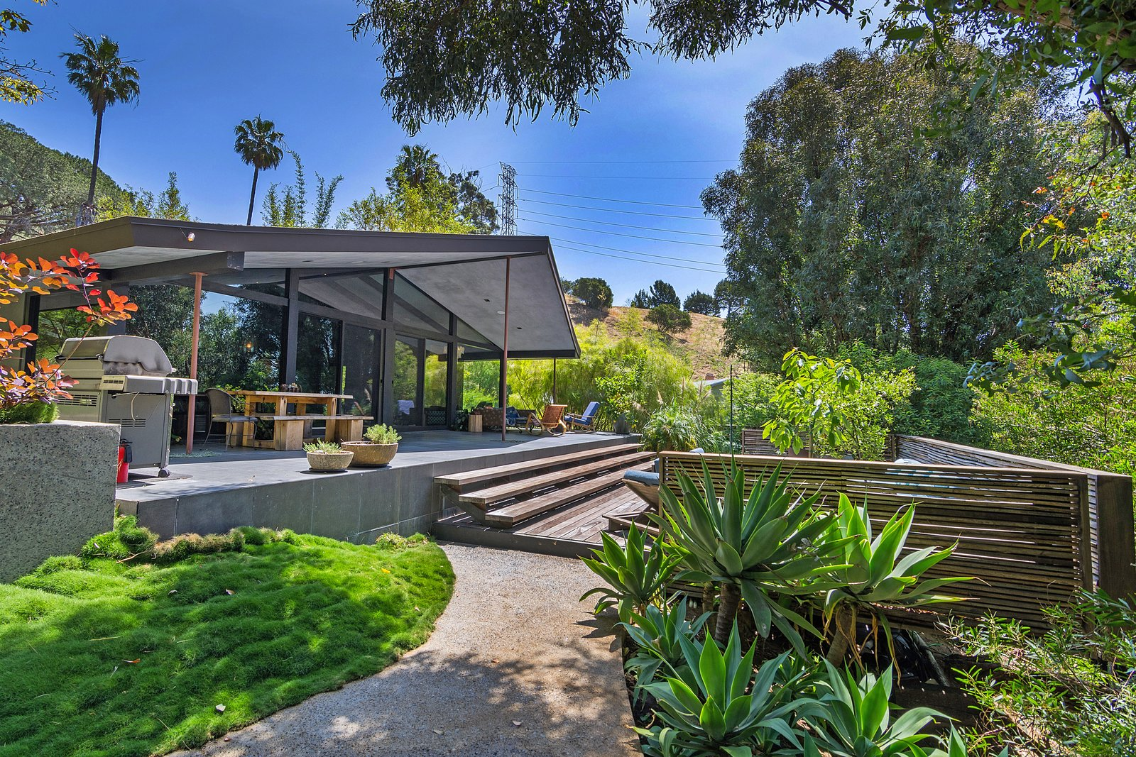 Tagged: Outdoor, Horizontal Fences, Wall, Wood Patio, Porch, Deck, Large Pools, Tubs, Shower, Back Yard, Grass, Trees, Concrete Patio, Porch, Deck, and Wood Fences, Wall.  Photo 1 of 14 in John Legend and Chrissy Teigen's Former Midcentury Home in the Hollywood Hills Is For Sale