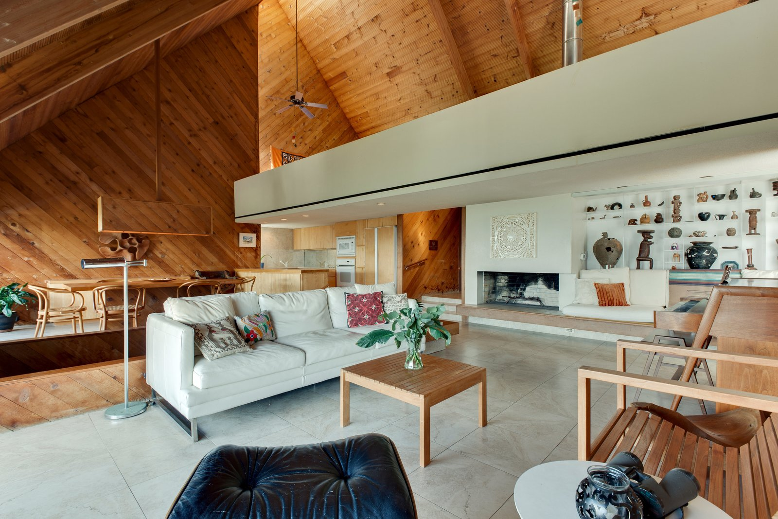 Tagged: Living Room, Wood Burning Fireplace, Chair, and Sofa.  Photo 9 of 13 in A Renowned Florida Architect's Geometric Family Home Hits the Market For the First Time