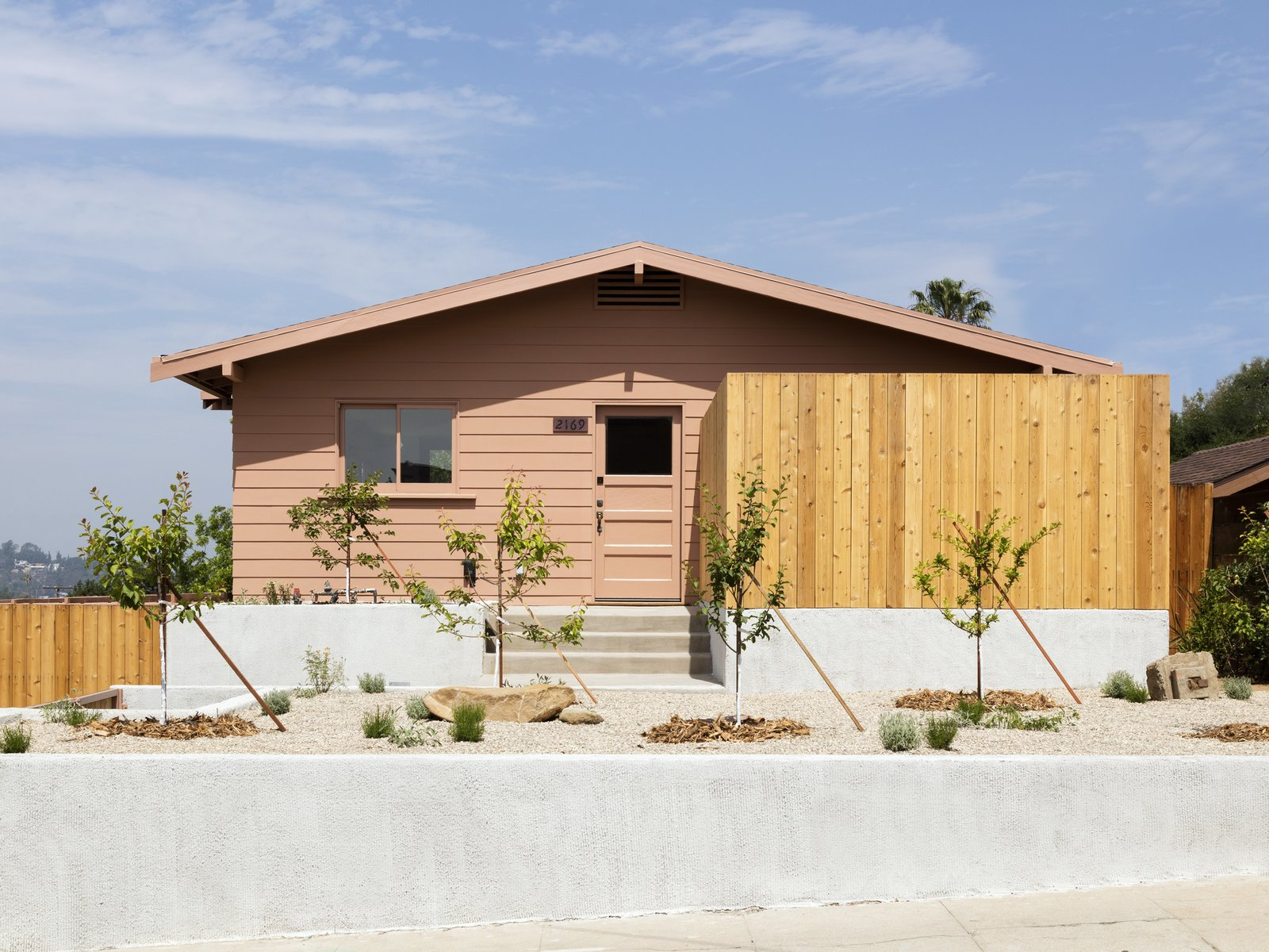 Tagged: Outdoor, Vertical Fences, Wall, Wood Fences, Wall, Front Yard, Hardscapes, and Boulders.  Photo 2 of 14 in Grids and Colors Inspire the Renovation of a Graphic Designer's Pink L.A. Bungalow