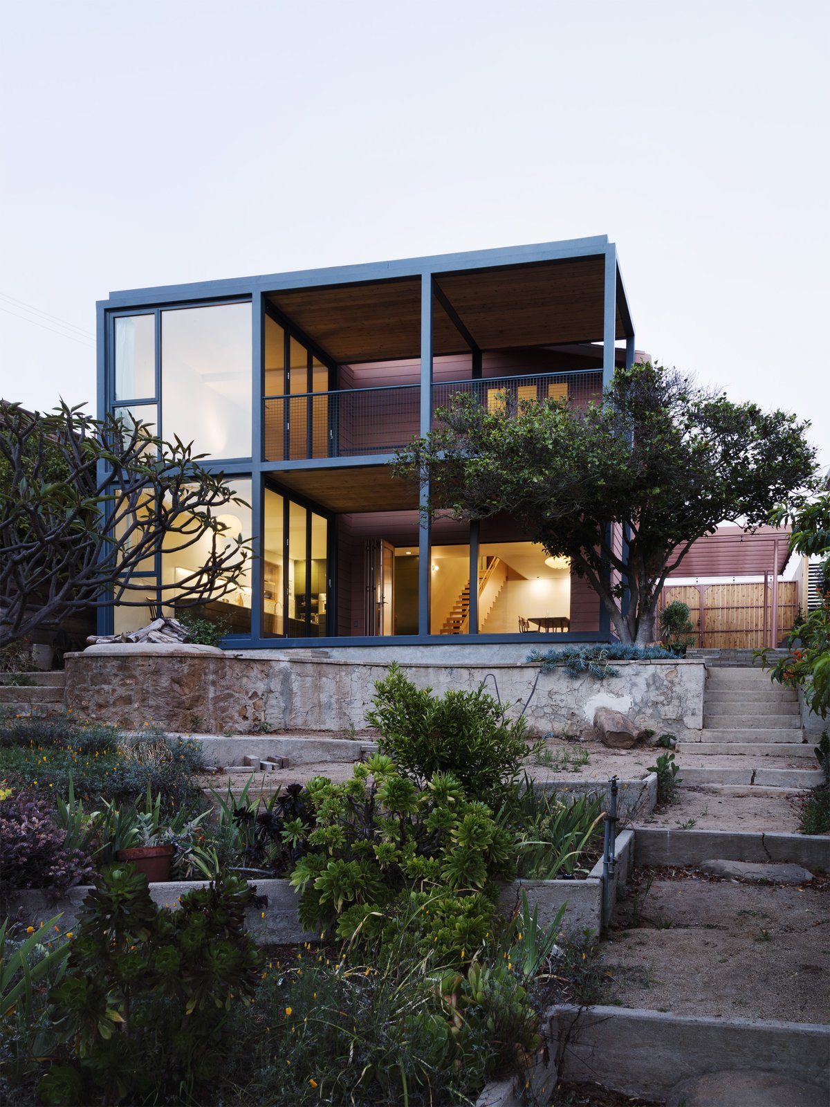 Tagged: Outdoor, Hardscapes, Trees, Vertical Fences, Wall, Large Patio, Porch, Deck, and Wood Fences, Wall.  Photo 3 of 14 in Grids and Colors Inspire the Renovation of a Graphic Designer's Pink L.A. Bungalow