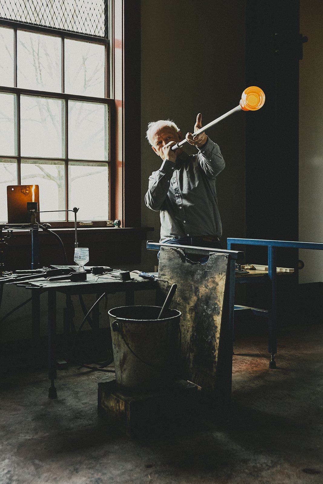 Designer Simon Pearce, shown at his factory in Windsor, Vermont, makes handblown glass the same way it's been made for thousands of years, by melting the raw ingredients in huge ovens, then gathering the molten material onto iron blowpipes. A finished Westport footed glass sits on a nearby workstation as a point of reference.