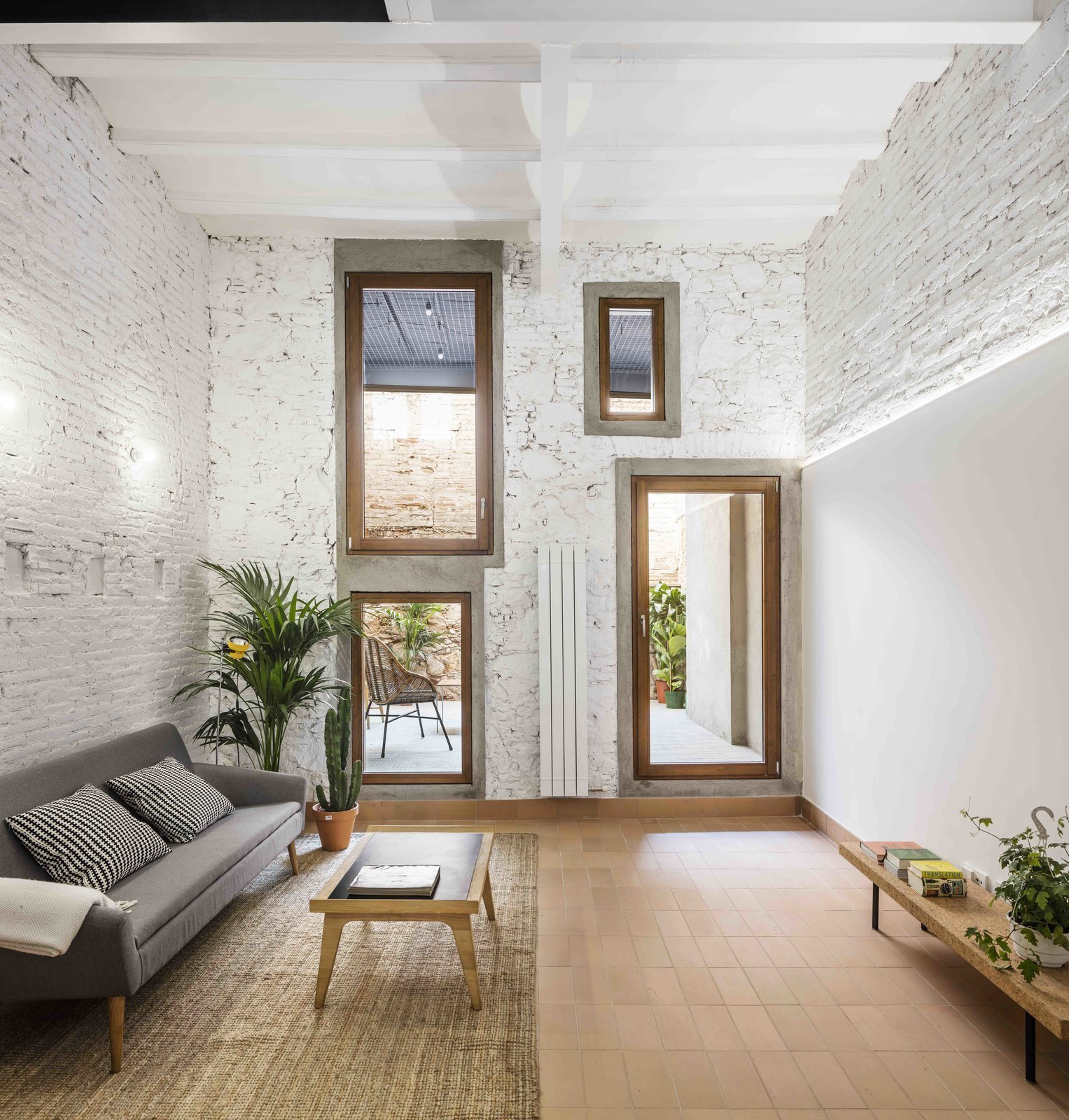 Tagged: Living Room, Coffee Tables, Sofa, Bench, and Wall Lighting.  Photo 10 of 13 in This Double-Height Apartment in   Barcelona Features Historic Details and a Floating Staircase