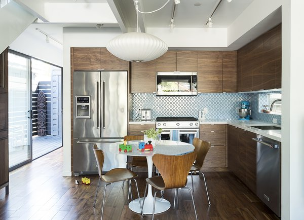 The dining  area features a custom Eero Saarinen table for Knoll and vintage Arne Jacobsen chairs for Fritz Hansen. KitchenAid appliances, IKEA cabinets, and Home Depot tile furnish the kitchen.