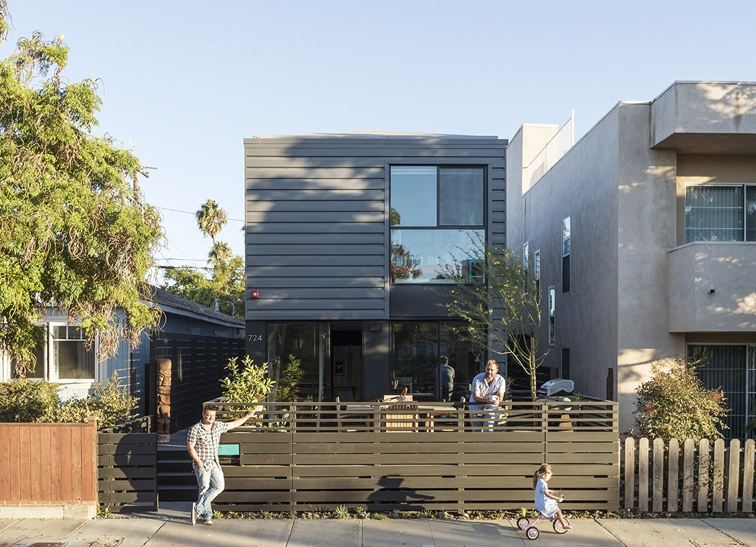 """""""We always knew we wanted to do  prefab—here it is something interesting and beautiful that adds to the character of the street,"""" says TJ (on deck, with Jay, left, and Chloe). """"There weren't many options for staying in the area with  a growing family,"""" notes Stott. - Santa Monica, California Dwell Magazine : July / August 2017 Tagged: Outdoor, Front Yard, Hardscapes, Trees, and Horizontal Fences, Wall.  Hill-Heiserman House by Dwell from A Family's Cramped Bungalow Is Replaced With an Accessible and Affordable Prefab"""