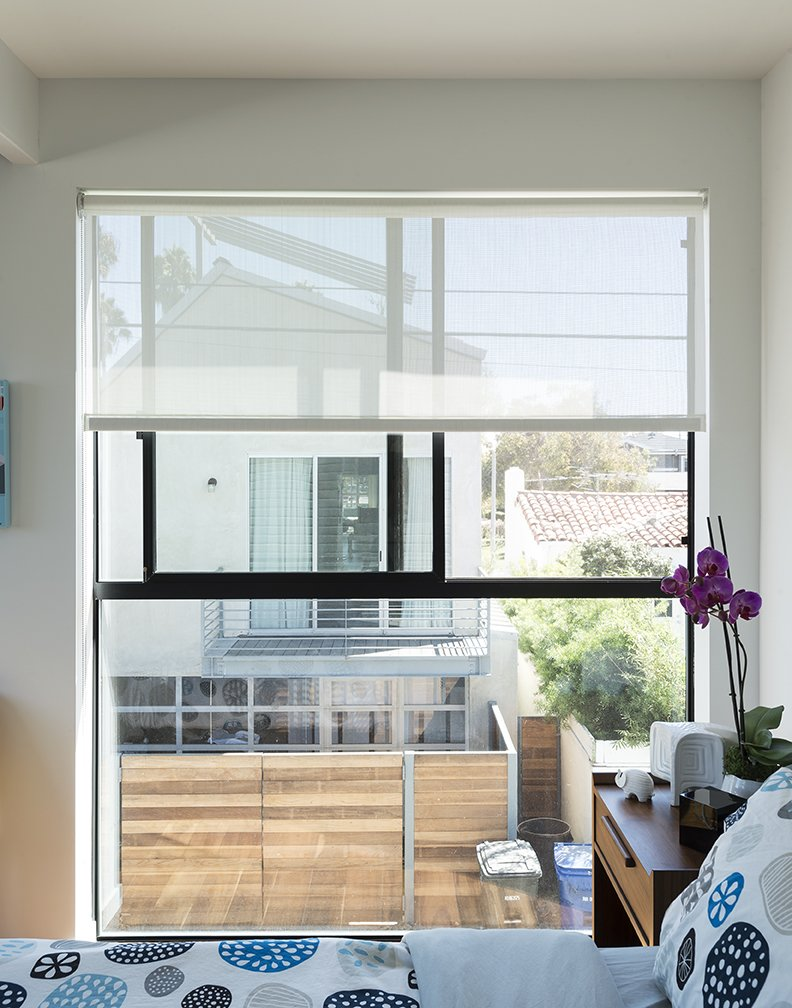 The master bedroom consists  of two modules set above a site-built garage. The fabric is from IKEA. - Santa Monica, California Dwell Magazine : July / August 2017 Tagged: Bedroom and Bed.  Hill-Heiserman House by Dwell from A Family's Cramped Bungalow Is Replaced With an Accessible and Affordable Prefab