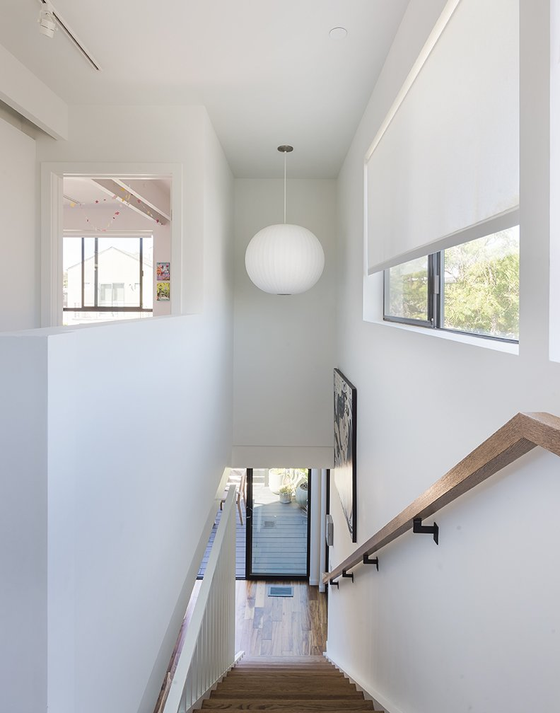 A George Nelson Bubble lamp hangs in the stairwell. - Santa Monica, California Dwell Magazine : July / August 2017 Tagged: Staircase and Wood Railing.  Photo 10 of 14 in A Family's Cramped Bungalow Is Replaced With an Accessible and Affordable Prefab