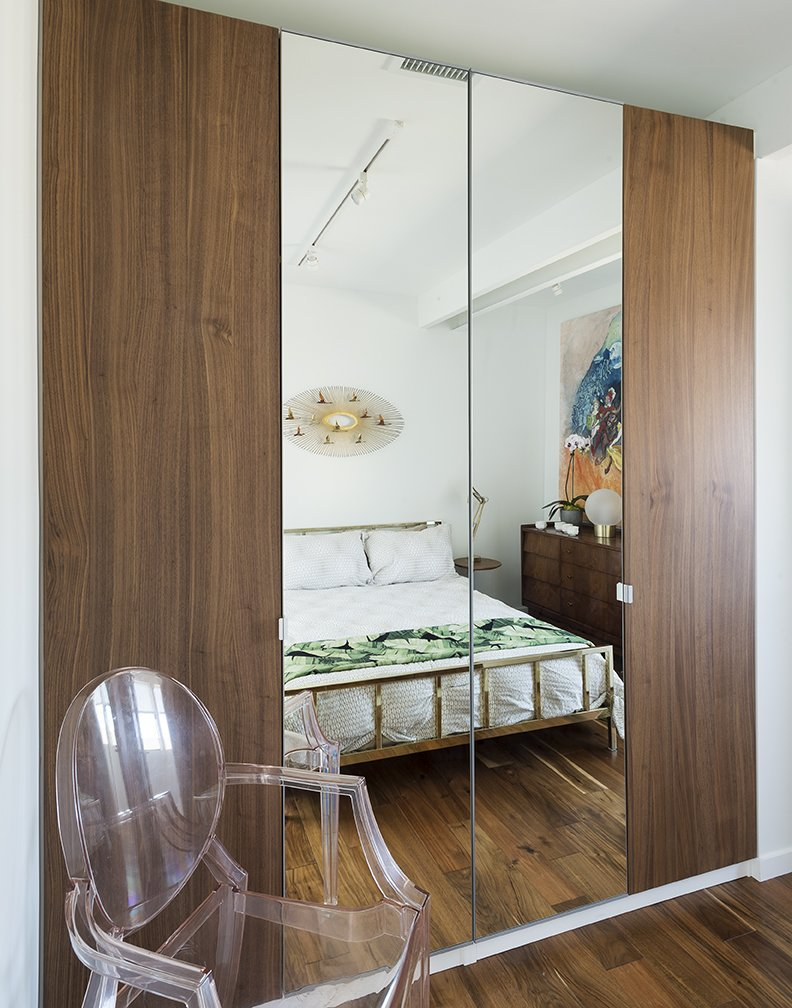 A Curtis Jere sculpture hangs  above a bed from CB2 in the upstairs guestroom. The Louis Ghost chair is by Philippe Starck  for Kartell. - Santa Monica, California Dwell Magazine : July / August 2017  Photo 11 of 14 in A Family's Cramped Bungalow Is Replaced With an Accessible and Affordable Prefab