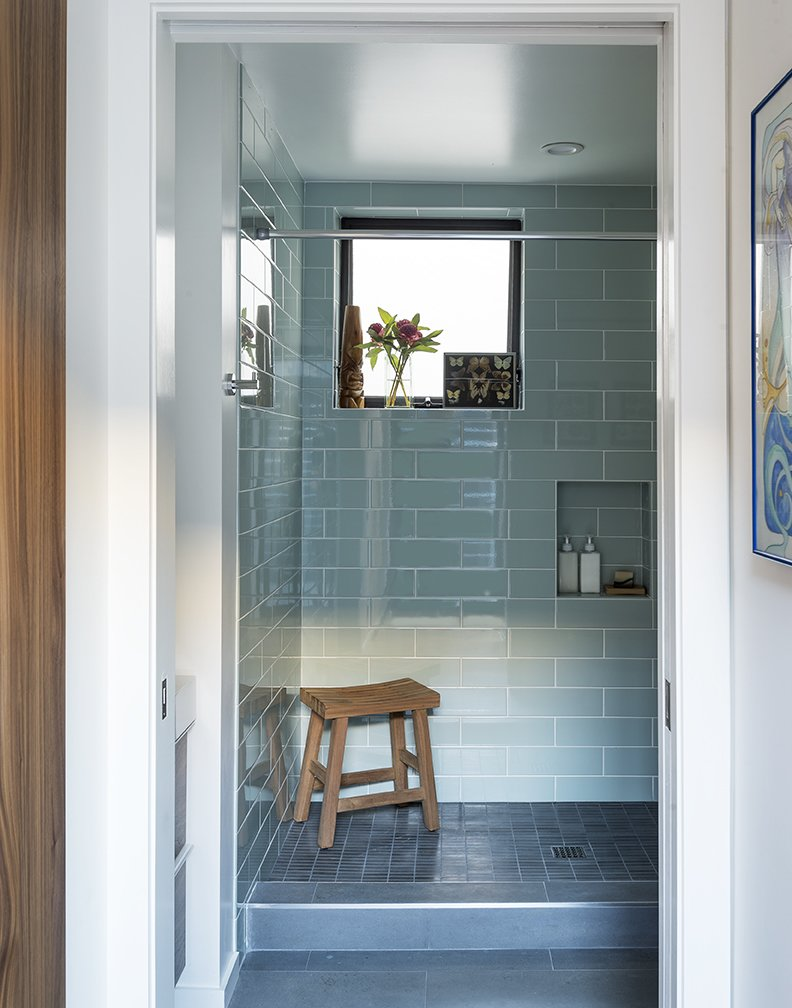 In the downstairs bathroom, the semigloss wall tile is from Daltile; the floor tile is by Deko. - Santa Monica, California Dwell Magazine : July / August 2017 Tagged: Bath Room, Recessed Lighting, Subway Tile Wall, Glass Tile Wall, and Open Shower.  Photo 12 of 14 in A Family's Cramped Bungalow Is Replaced With an Accessible and Affordable Prefab