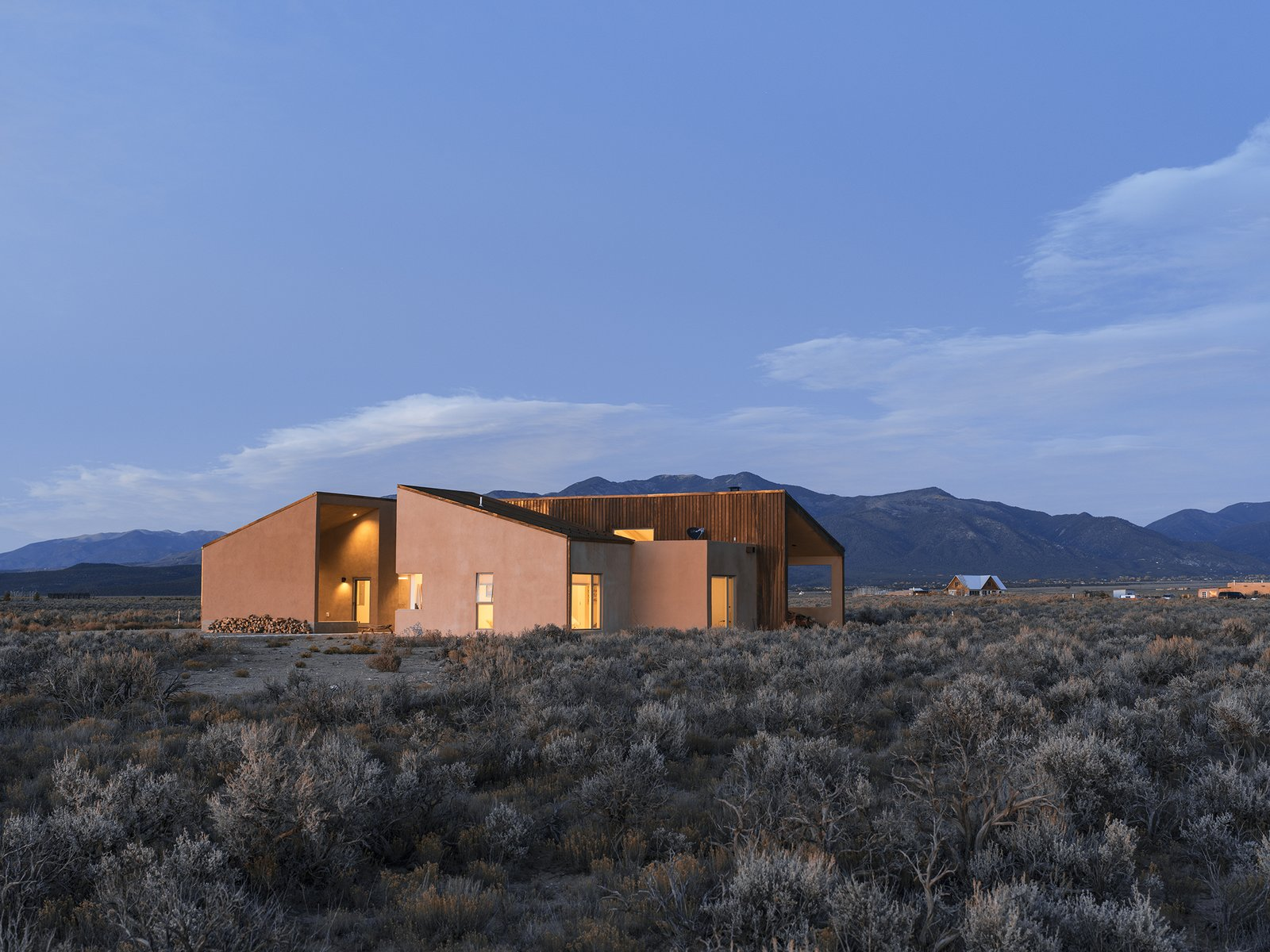 """On a five-acre property outside Taos, New Mexico, designer Molly Bell worked closely with her father, builder Ed Bell, to create a new residence for owner Lois Rodin. """"Lois requested that it appear as a grouping of individual masses, so that it read more like a cluster than a solitary shape,"""" Molly says. """"I hope it shows that it's OK to do something modern in such a traditional environment, and not to be afraid of it."""" - Taos, New Mexico Dwell Magazine : July / August 2017 Tagged: Desert, Shrubs, Exterior, Stucco Siding Material, House, and Wood Siding Material.  Photo 2 of 11 in A Rookie Designer and Her Builder Father Create an Artist's Sculptural Loft in the Desert"""