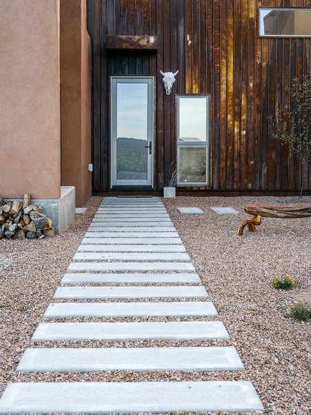 Rusted metal, used on three of the home's five roofs, extends to the entrance facade, which, in a nod to northern New Mexico's haciendas, opens to a courtyard. Rather than buy pre-rusted siding, Molly and her father oxidized the steel themselves.