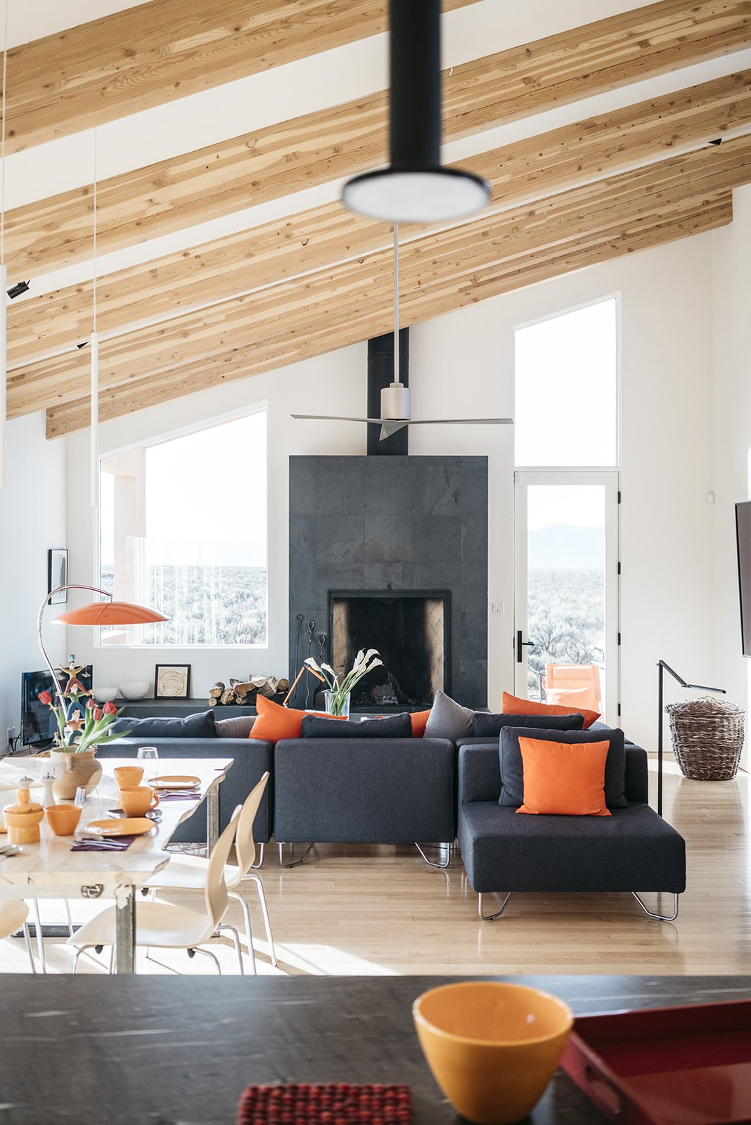 The living/dining room occupies a long, high-ceilinged space. The sectional is from CB2. Tagged: Living Room, Sectional, Table, Chair, Standard Layout Fireplace, and Table Lighting.  Photo 4 of 11 in A Rookie Designer and Her Builder Father Create an Artist's Sculptural Loft in the Desert