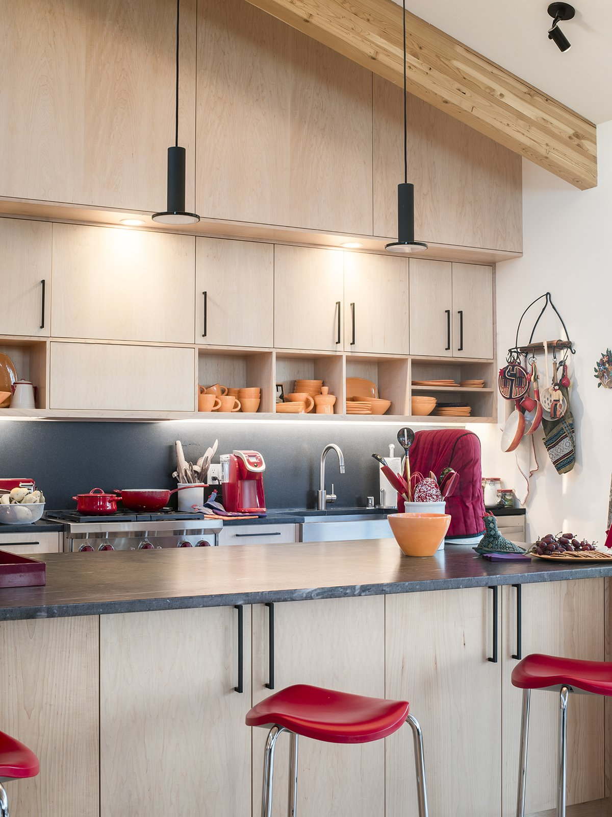 The kitchen cabinets hold dishes by Butterpie Productions. Tagged: Kitchen, Ceiling Lighting, Drop In Sink, Range, and Wood Cabinet. A Rookie Designer and Her Builder Father Create an Artist's Sculptural Loft in the Desert - Photo 5 of 11
