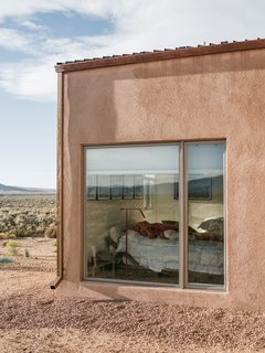 "A Rookie Designer and Her Builder Father Create an Artist's Sculptural Loft in the Desert - Photo 5 of 10 - A gravel perimeter keeps mud from splashing on the walls when it rains. Adds Molly, ""You can get away with minimal landscaping because there's so much natural vegetation here."""