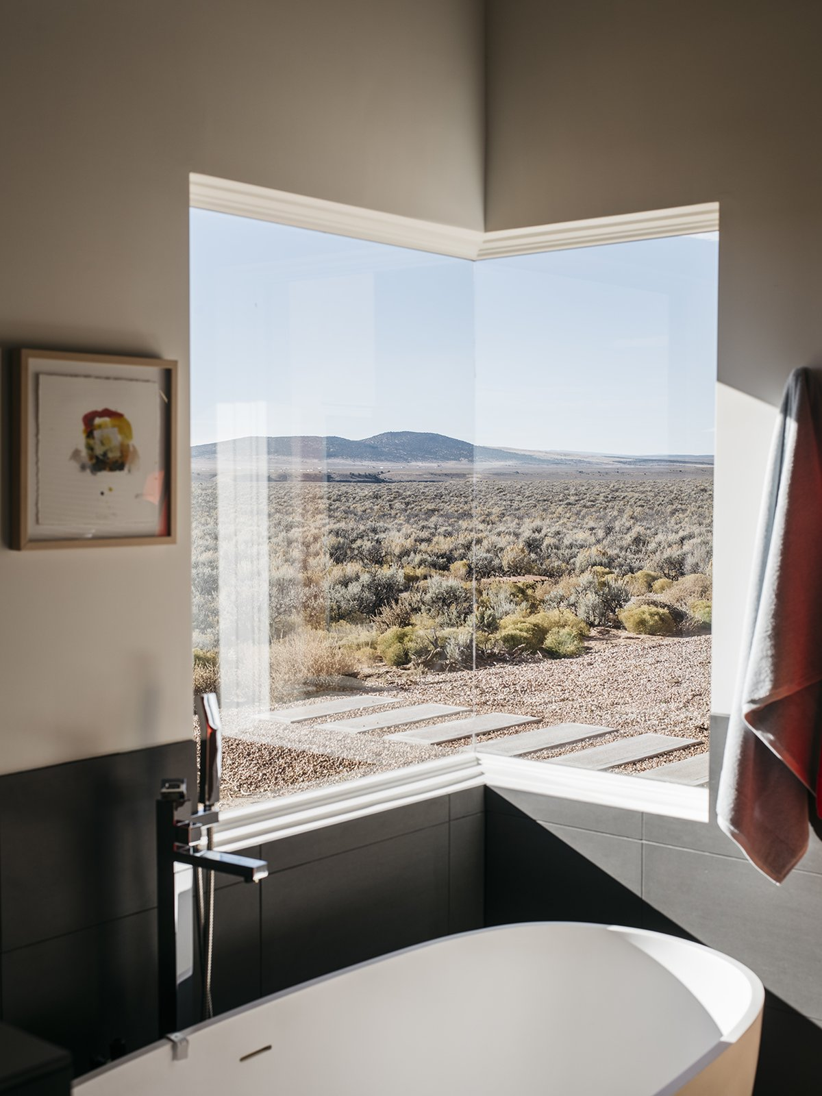 "The master bathroom features one of two corner windows in the house. ""At night, when I take a bath, I can see the moon and the stars,"" says Lois. - Taos, New Mexico Dwell Magazine : July / August 2017 Tagged: Bath Room and Freestanding Tub.  Photo 8 of 11 in A Rookie Designer and Her Builder Father Create an Artist's Sculptural Loft in the Desert"