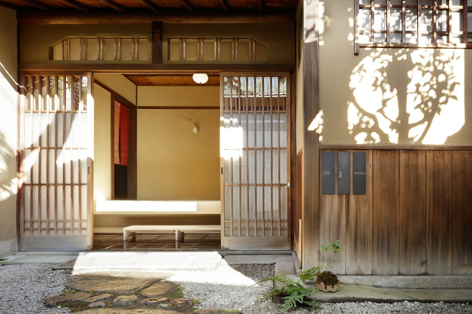 Fukoka-based firm CASE-REAL executed a renovation of the century-old residence in 2015, creating functional zones that would serve their clients' lifestyles and accommodate guests: a tea room, gallery space, office, and guest room. The modern aesthetics of the townhouse are surrounded by the thick, clay walls of a traditional Japanese warehouse, a rarity in historic memory in the neighborhood.  The thoughtfully detailed interior make for quiet, comfortable spaces that evoke a calming energy and look out at seasonal environments.   Tagged: Outdoor, Garden, Walkways, and Hardscapes.  Photo 4 of 13 in A Minimalist Townhouse Provides Serene Accommodations in Historic Kyoto