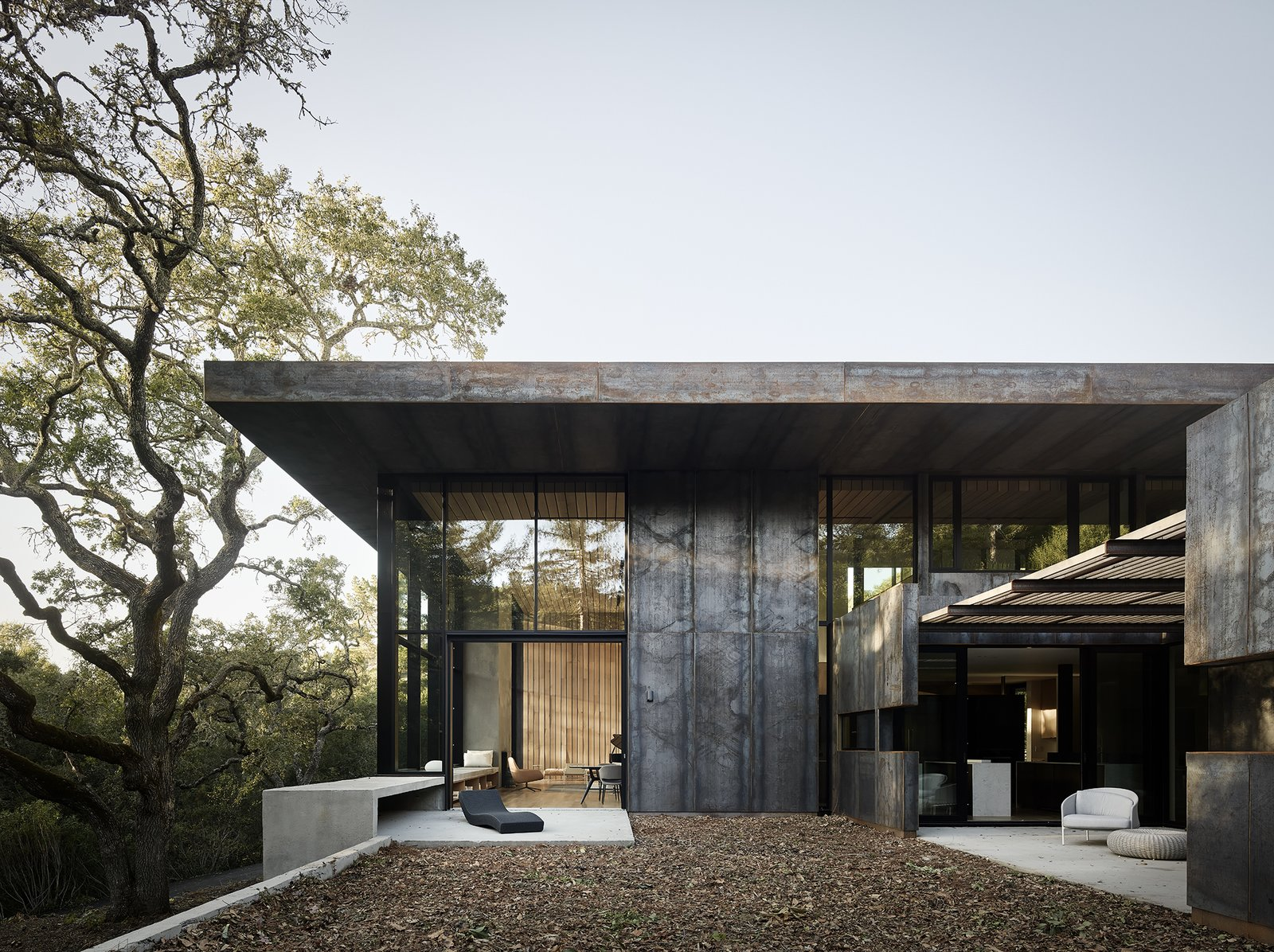 Located in Orinda, California, a three-bedroom house by architect Greg Faulkner took its first aesthetic cue from a large oak tree on the site. Cor-Ten steel panels clad the exterior, while white oak offers a material counterpoint on the interior. A 12-foot-wide sliding pocket wall opens the living/dining area to a terrace with a Wave Chaise longue by Paola Lenti. The landscape design is by Thuilot Associates. Tagged: Exterior, House, Metal Roof Material, Metal Siding Material, and Flat RoofLine.  Photo 2 of 14 in Nature Drove the Design of This Sculptural, Cor-Ten Steel House in Northern California