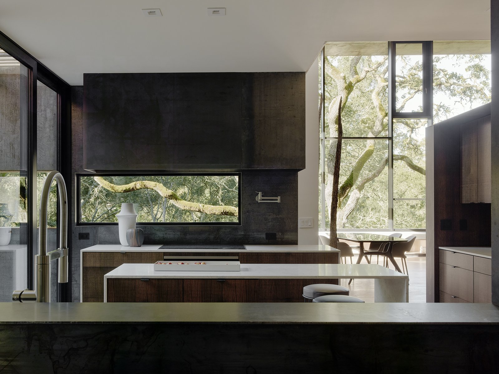 In the kitchen, bar stools by Living Divani pull up to an island with Bretonstone countertops; the faucet is by Blanco. Tagged: Kitchen and Wood Cabinet. Nature Drove the Design of This Sculptural, Cor-Ten Steel House in Northern California - Photo 4 of 14