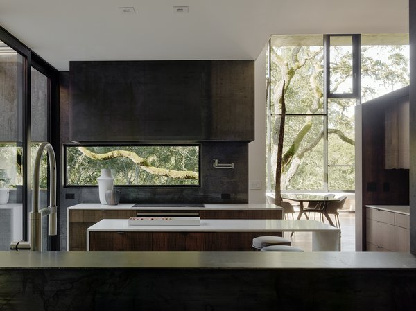 In the kitchen, bar stools by Living Divani pull up to an island with Bretonstone countertops; the faucet is by Blanco.