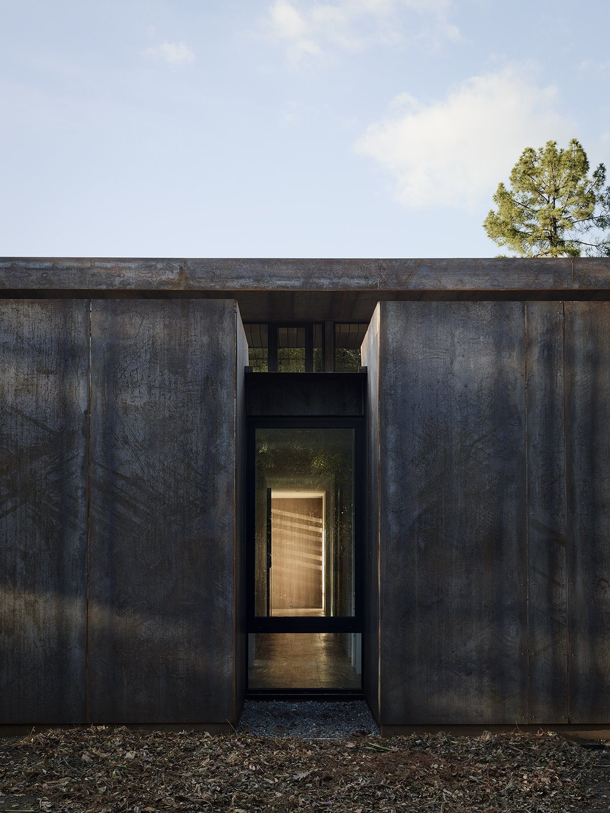Overlooking the double-height living/dining area is the mezzanine level, where the master suite and office are located. Tagged: Exterior and Metal Siding Material. Nature Drove the Design of This Sculptural, Cor-Ten Steel House in Northern California - Photo 7 of 14