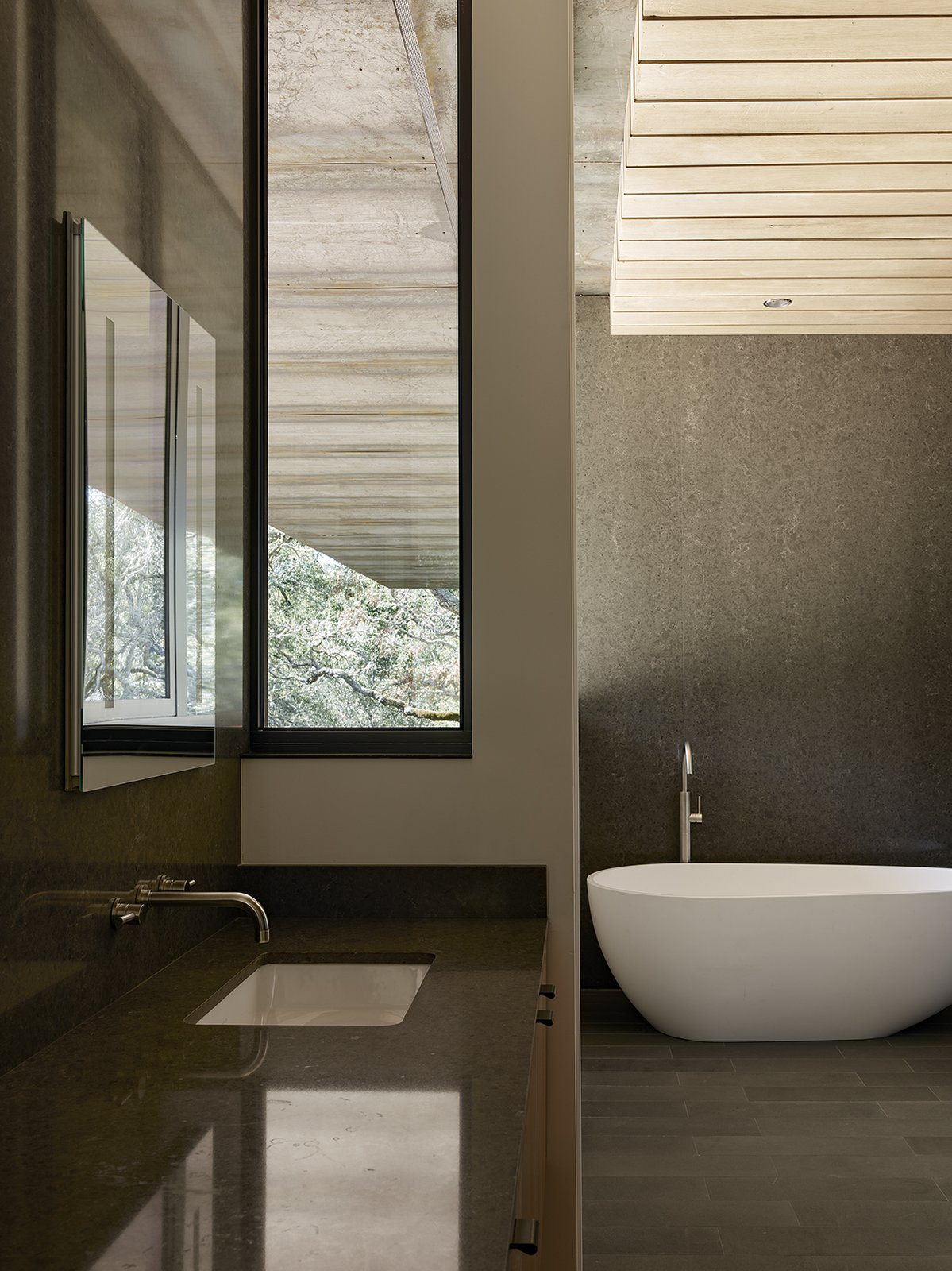In the master bathroom, a tub and sink from ADM join Cifial fixtures. Tagged: Bath Room, Concrete Wall, Granite Counter, Undermount Sink, Freestanding Tub, and Recessed Lighting.  Photo 12 of 14 in Nature Drove the Design of This Sculptural, Cor-Ten Steel House in Northern California