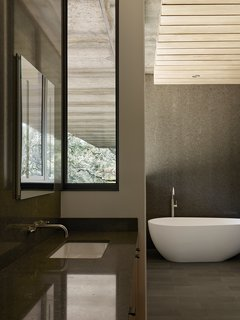 Nature Drove the Design of This Sculptural, Cor-Ten Steel House in Northern California - Photo 11 of 13 - In the master bathroom, a tub and sink from ADM join Cifial fixtures.