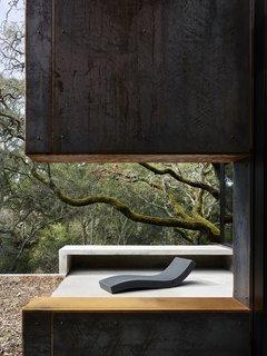 Nature Drove the Design of This Sculptural, Cor-Ten Steel House in Northern California - Photo 12 of 13 - An opening in a Cor-Ten steel—clad wall on the terrace frames the Paola Lenti chaise longue.