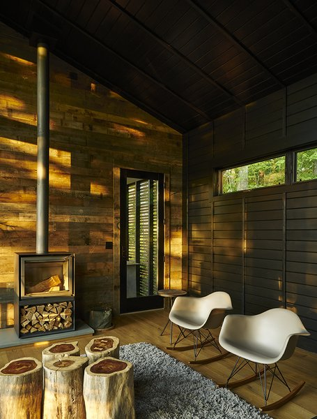 A little cottage in North Carolina  is furnished with a cluster of wood-stump end tables by Urbia,  two Eames rockers, and a 16-H wood-burning stove by Stûv.