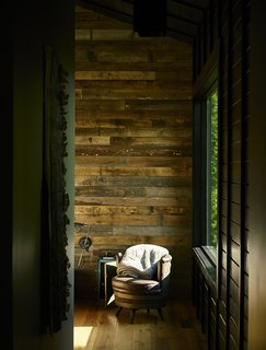 A Rustic-Modern Cabin Inspired by Japanese Bungalows and Shou Sugi Ban - Photo 4 of 12 - In each room, a single wall was clad in reclaimed poplar. An antique barrel chair sits in the master bedroom.