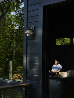 A Rustic-Modern Cabin Inspired by Japanese Bungalows and Shou Sugi Ban - Photo 10 of 12 - A recessed sliding door by Jeld-Wen opens from the kitchen onto a perch deck.