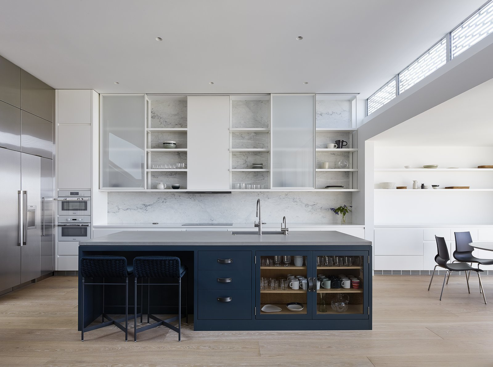 The home's kitchen features dual Miele ovens, Thermador refrigerator and freezer, and Thermador induction cooktop. A feature wall clad in natural Carrara marble sits behind sliding cabinet uppers. Paola Lenti Heron counter stools in 'verde scuro,' coordinate with custom cabinet fronts, accented with Spinneybeck leather pulls. Tagged: Kitchen, White, Light Hardwood, Marble, Ceiling, Recessed, Refrigerator, Wall Oven, Range, Ice Maker, Drop In, and Open.  Best Kitchen Light Hardwood Drop In Photos from A Historic Victorian in San Francisco Is Meticulously Transformed Into a Modern Family Home