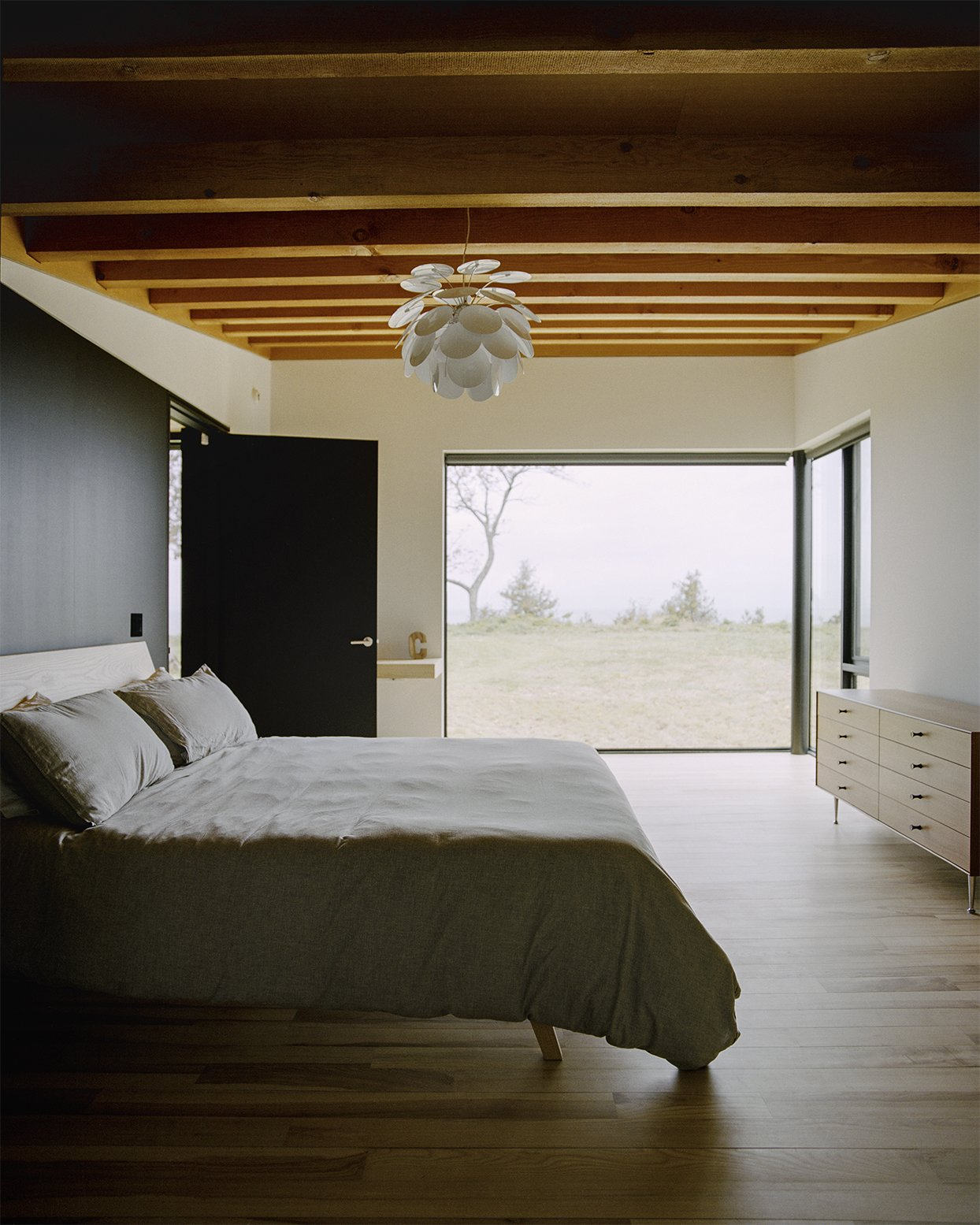 In the master bedroom, the ash bed was designed by Desai Chia  and fabricated by Gary Cheadle  of Woodbine; the dresser is by  George Nelson for Herman Miller. Panes by Western Windows  appear throughout the home. - Leelanau County, Michigan Dwell Magazine : September / October 2017 Tagged: Bedroom, Dresser, Light Hardwood Floor, Shelves, Bed, and Pendant Lighting.  Best Photos from Plagued Ash Trees Were Repurposed to Create This Charred-Cedar Clad Home on Lake Michigan