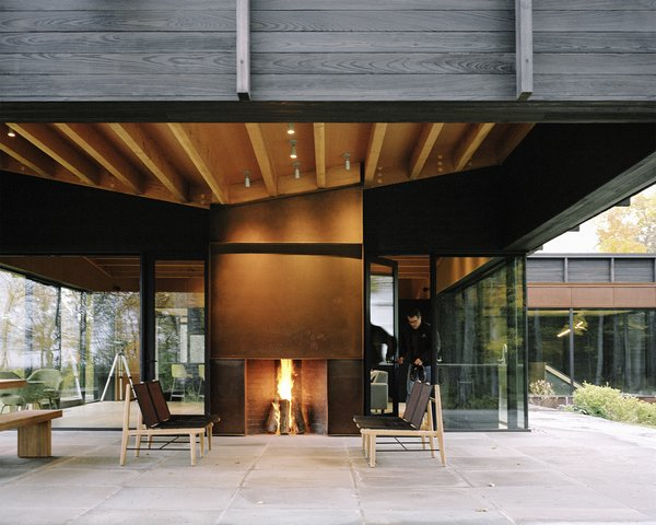The home's undulating roof, composed of exposed wood beams and plywood sheathing, references the rolling terrain. A Cor-Ten steel–clad outdoor fireplace was built by BRD Construction; the same material was used for the interior fireplace, as surround on some windows, as cladding for the garage door, and on the chimney. The lounge chairs are from the Finn Collection from Design Within Reach. Tim Kirby of Surface Design Inc. tackled  the site's landscape architecture.