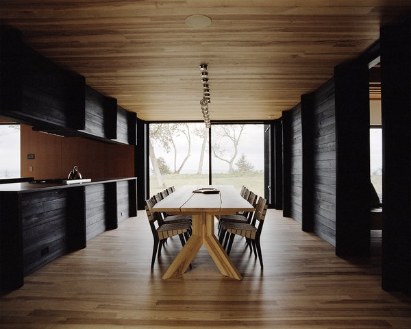 The dining area features an ash table designed by Desai Chia and created by Gary Cheadle. The chairs are by Jens Risom.