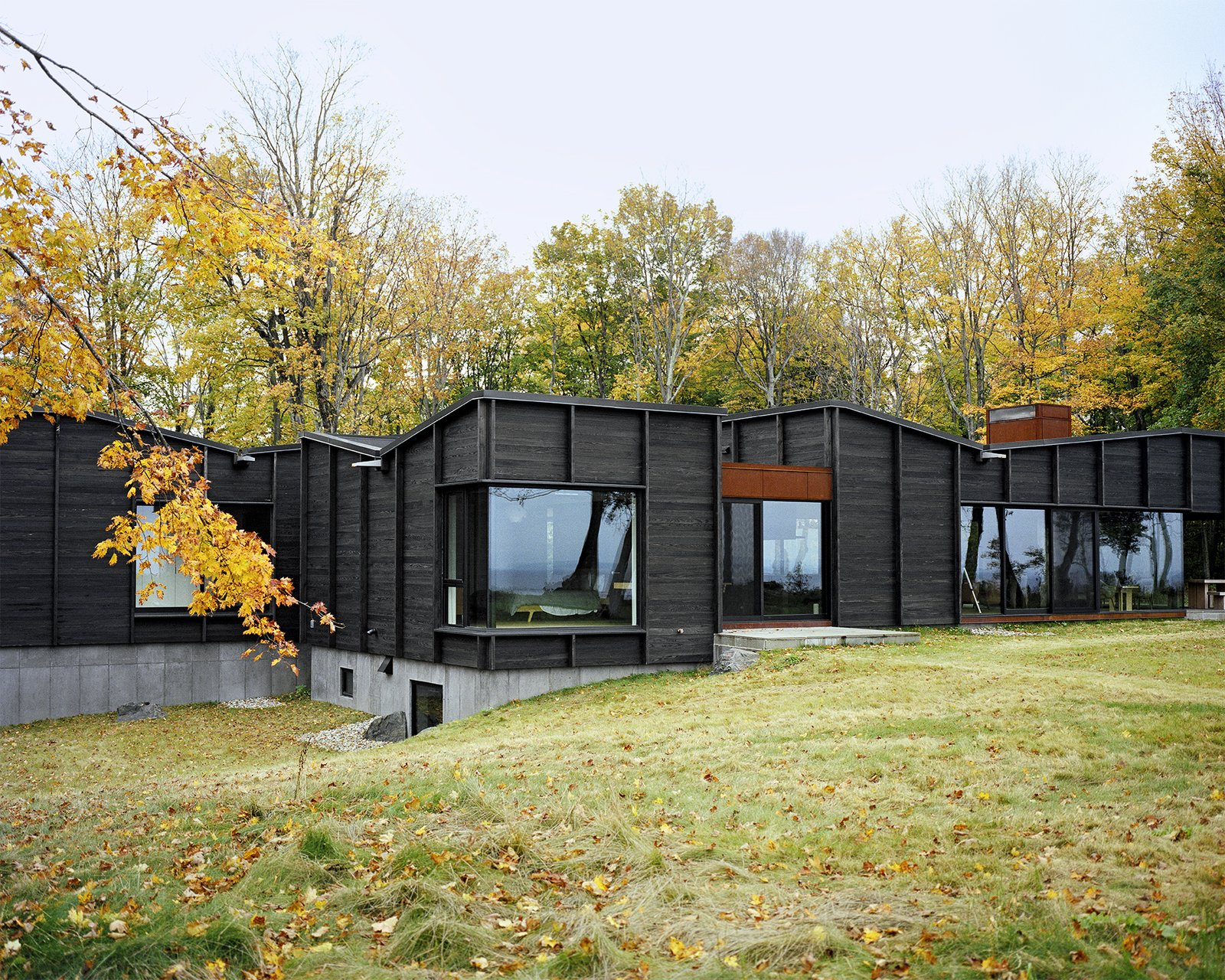 Three interconnected structures—one for communal spaces, one for the master suite, and one for the three children's bedrooms—are linked via a glass-enclosed breezeway that also serves as the entrance and dining area. - Leelanau County, Michigan Dwell Magazine : September / October 2017 Tagged: Exterior, House, and Wood Siding Material.  Best Photos from Plagued Ash Trees Were Repurposed to Create This Charred-Cedar Clad Home on Lake Michigan