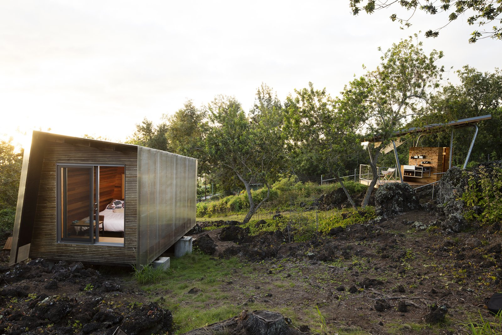 "Moore worked with contractor David Sharp to ensure that the pavilions, each measuring under 120 square feet, would sit lightly on the sloping site. ""A big structure would have been about the house, and not the place,"" she says. ""Having multiple units was important.""  Maui, Hawaii Dwell Magazine : September / October 2017 Tagged: Exterior, House, Metal Roof Material, Wood Siding Material, and Metal Siding Material.  Photo 3 of 9 in Two Tiny Pavilions Respectfully Perch Atop a Lava Flow on Maui"
