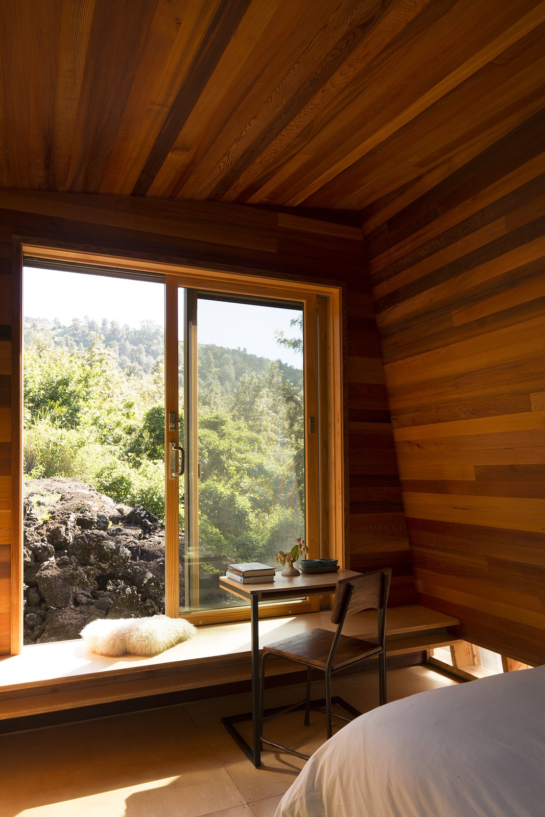 Detailed in cedar paneling and plywood, Mauka was oriented to catch the sunrise. The table is by Moore's firm, FLOAT.  Maui, Hawaii Dwell Magazine : September / October 2017 Tagged: Windows, Sliding Window Type, and Wood.  Best Photos from Two Tiny Pavilions Respectfully Perch Atop a Lava Flow on Maui