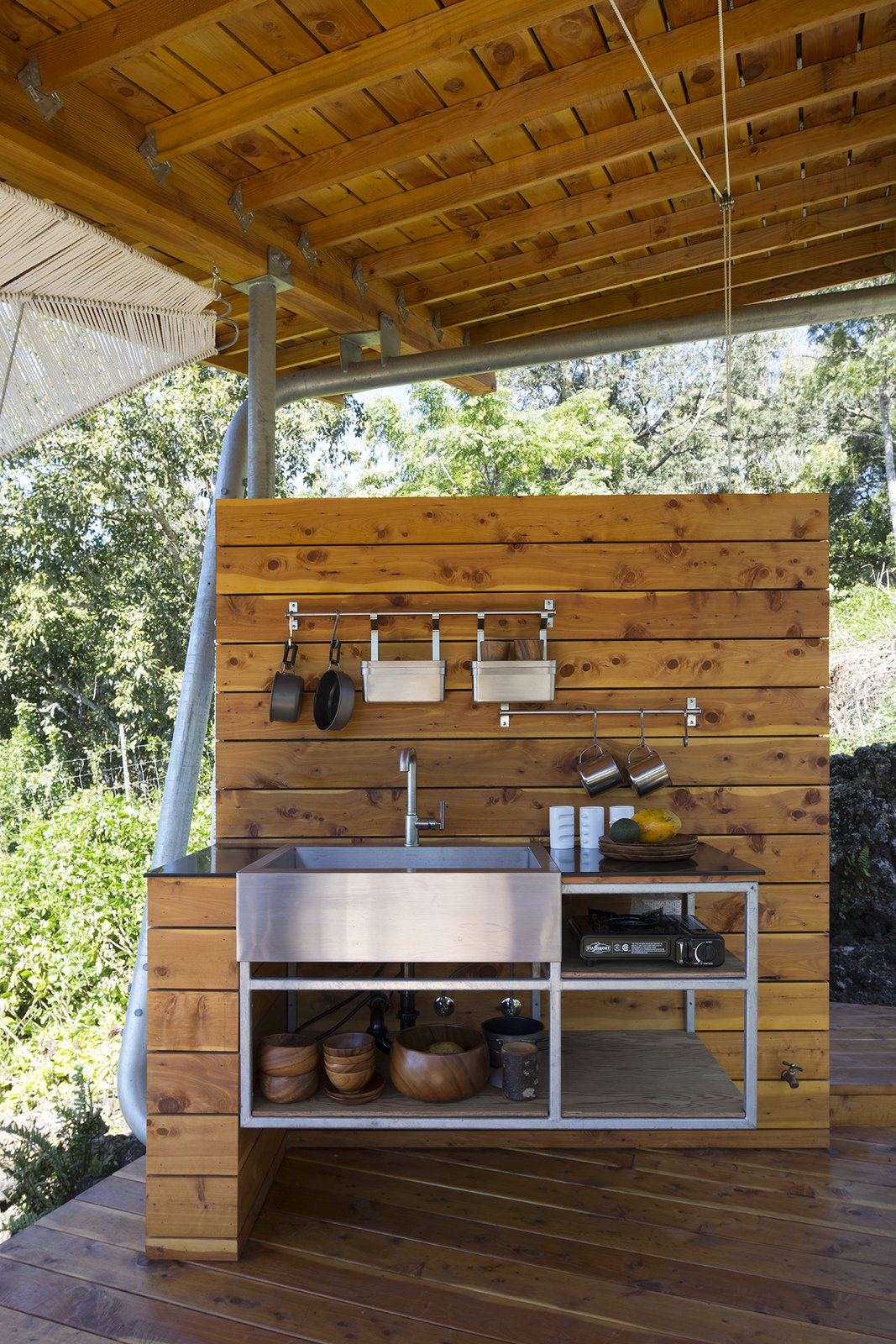 The kitchen contains a Kohler sink and pot racks from IKEA.  Photo 8 of 9 in Two Tiny Pavilions Respectfully Perch Atop a Lava Flow on Maui