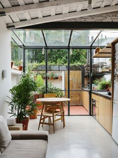 An Architect Turns His Small, Dark Apartment in Buenos Aires Into a Bright and Airy Home - Photo 1 of 10 - A steel and glass structure wraps one end of the apartment, adding the illusion of greater space to the 720-square-foot home.