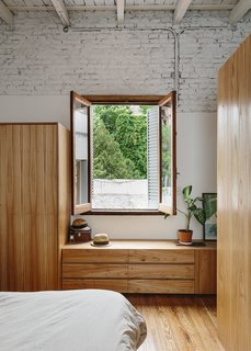 """An Architect Turns His Small, Dark Apartment in Buenos Aires Into a Bright and Airy Home - Photo 5 of 10 - Demolition exposed a high, wood-beamed ceiling, which added """"cubic meters of air"""" to the apartment, says Hernán. The bedroom is furnished with custom pieces made of Paraiso wood."""
