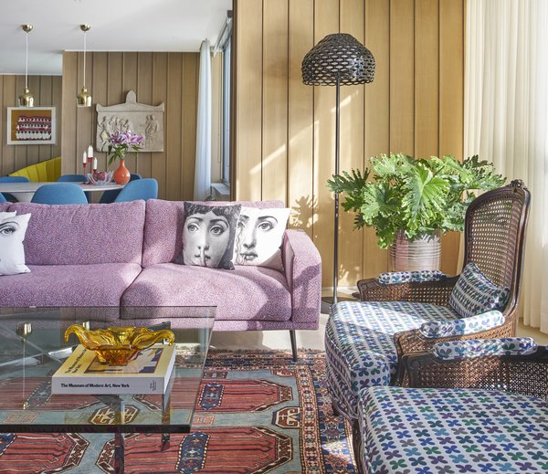 Eleni Katsarou's new Chicago apartment is an explosion of color. Graphic Fornasetti pillows rest on a pixelated-pink Carlton sectional by BoConcept next to cane back chairs upholstered in Quatrefoil fabric by Alexander Girard.