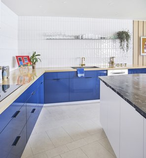 An Interior Designer Helps His Mother Turn Her 1960s Chicago Apartment Into a Colorful Haven - Photo 3 of 8 - A wood countertop with blue laminate cabinets underneath contrasts with a white island topped with travertine. The wall tile is Origin Birch White by AKDO, and the brass faucet is by California Faucets. As in the rest of the apartment, the flooring is colored cork from Globus Cork.