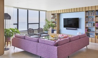 An Interior Designer Helps His Mother Turn Her 1960s Chicago Apartment Into a Colorful Haven - Photo 4 of 8 - From the 33rd floor, the view of Lake Michigan is expansive. Linen curtains from The Shade Store filter sunlight. Extra lighting is provided by LED ceiling lights, a Tatou F floor lamp by Patricia Urquiola, and a Copycat table lamp by Michael Anastassiades for Flos.