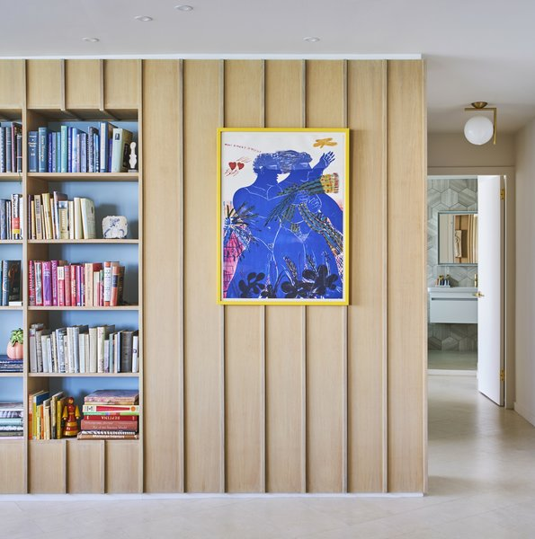 An Alekos Fassianos lithograph and soft blue niches offset the wood paneling. An IC lamp by Michael Anastassiades hangs in the hallway.