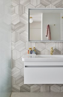 An Interior Designer Helps His Mother Turn Her 1960s Chicago Apartment Into a Colorful Haven - Photo 6 of 8 - The bathroom's hexagonal marble tiles are by Ann Sacks, and the fixture, mirror, and wall cabinet are all by Duravit.