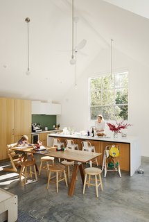 Dwell's Top 10 Renovations of 2017 - Photo 2 of 10 - Formerly a one-bedroom cabin, the Mill Valley, California, home of Tim and Stefanie Rosa more than doubled in size after a renovation and addition by Pfau Long Architecture. The high-ceilinged kitchen-living-dining room is outfitted with white oak casework by Henrybuilt. Leo, five, sits in a Tripp Trapp chair at a custom dining table.